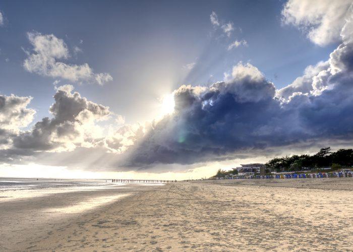 Sonne bricht durch Wolken über Strand